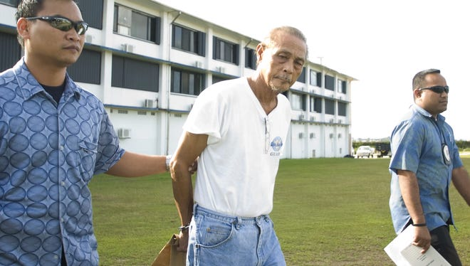 In this May 2009 file photo, Serafin Pablo, 64, center, is escorted out of the Guam Police Department Criminal Investigation Division in Tiyan after his arrest on May 28.