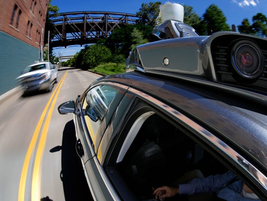 A self-driving Uber drives in Pittsburgh during a media