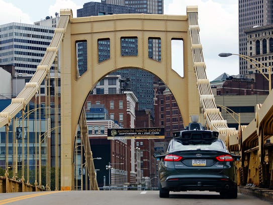 A self driving Uber Ford Fusion drives across the ninth