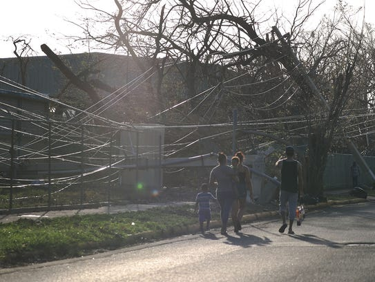 Power lines and trees are seen knocked over by the
