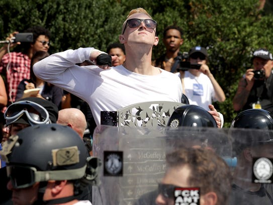 "A man makes a slashing motion across his throat toward counter-protesters as he marches with other white nationalists, neo-Nazis and members of the ""alt-right"" during the ""Unite the Right"" rally Aug 12, 2017 in Charlottesville, Va."