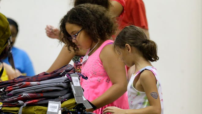 Volunteers from the Boys and Girls Club of the Fox Valley fill backpacks was part of the Backpacks for Kids Campaign at Post-Crescent Media on Aug. 5, 2015 in Appleton.
