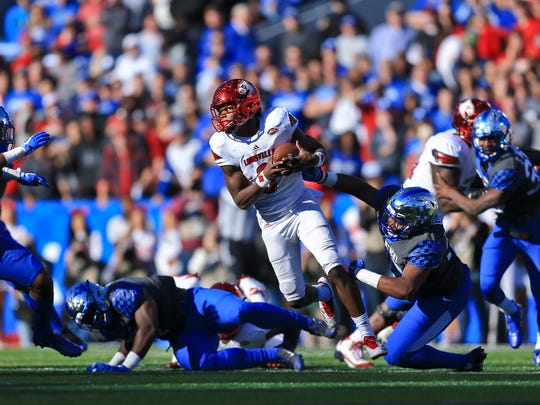 """Louisville's Lamar Jackson scrambles away from the Kentucky defense while the Cards easily beat the Wildcats 44-17 Saturday at Kroger Field. """"I can't recall defending anybody as talented as he is,"""" Mark Stoops said, describing Lamar Jackson."""