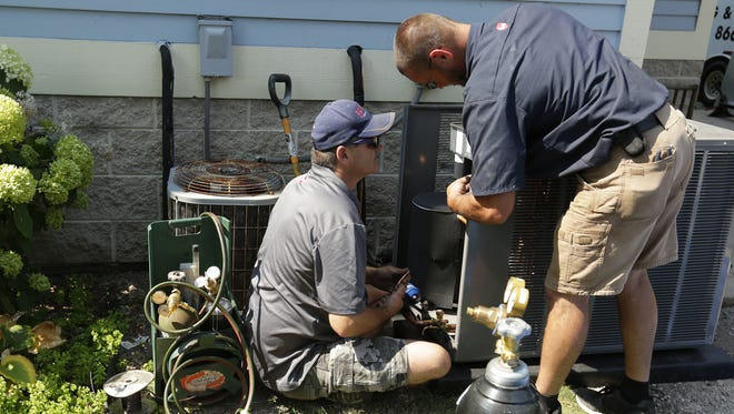 Mike Madison and Dan Kasuboski of Brewer Heating and Cooling install a new air conditioner on Wednesday, August 2, 2017, at the Christine Ann Center in Oshkosh. The center received donations through the community and businesses to fix the most needed of the problems that plagued the building.  An air conditioner was donated by Design Air of Kimberly and installed by Brewer Heating and Cooling of Ripon.