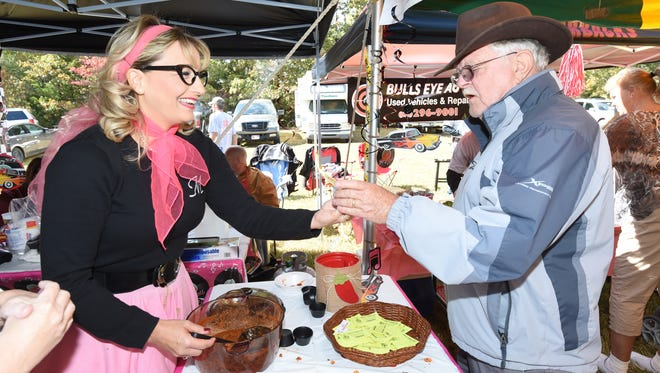 Integrity First Bank chili team member Melanie Britt, left, serves chili to Mountain Home resident Philip Chartrand in Lakeview on Saturday during the 20th Annual Hillbilly Chili Cook-off. Several hundred people gathered for the event.