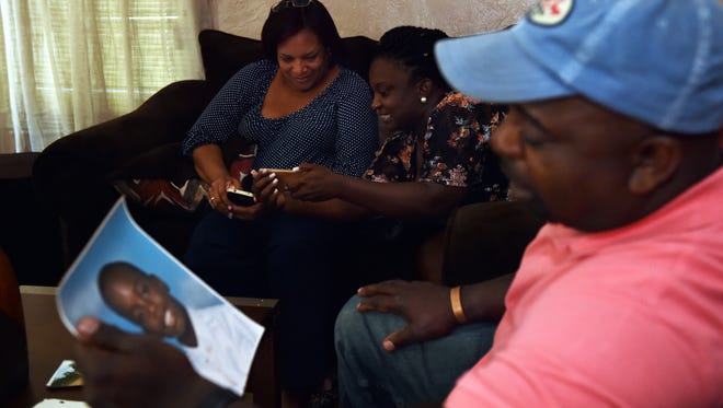 Angela Johnson, from left, Jerrica Gaines and Melvin Mangum Sr. look through photographs of Melvin Mangum Jr. while recalling fond memories at a home in Jackson Wednesday. Melvin Mangum Jr. died at age 18, May 22.