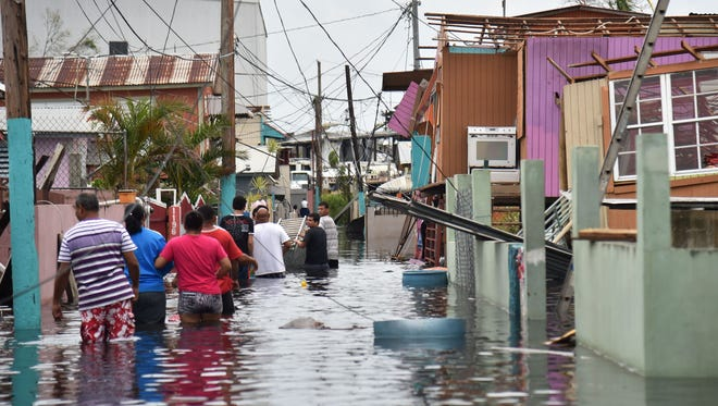 People walk in a flooded street next to damaged houses in Catano town, in Juana Matos, Puerto Rico, on Sept. 21, 2017, after it was pummeled by Hurricane Maria.
