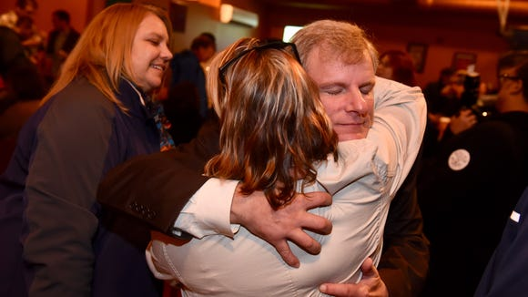 Michael Helfrich embraces a supporter during his election