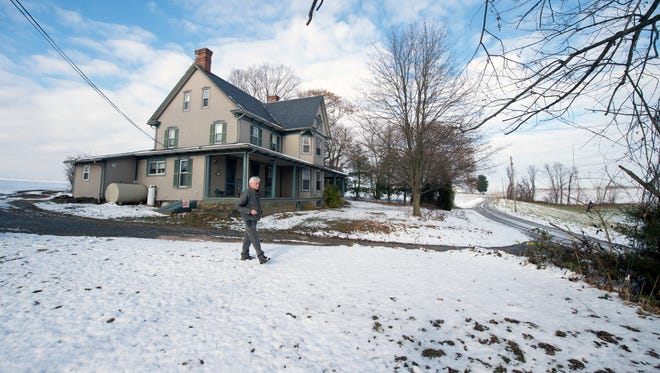 Randy Stewart walks in front of his home in Lower Chanceford Township that was built in 1910. His farm has been in the family for nearly 200 years. A high-voltage transmission line may be built across the end of the gravel township road, at top right. Stewart Road, where it intersects with Good Road.