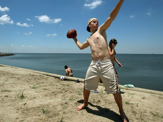 Neale Smith tosses a football on Lake Pontchartrain