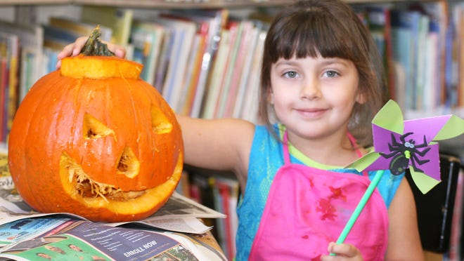 Savannah Campbell, 4, of Hopewell shows off her pinwheel craft and carved pumpkin during a children's program at Cumberland County Library.