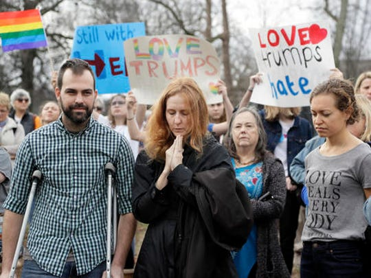 People take part in a protest Friday, Jan. 20, 2017, in Nashville, Tenn., organized to combat harsh rhetoric by Donald Trump. The protesters observed 15 minutes of silence during the time Trump took the Presidential oath of office in Washington.