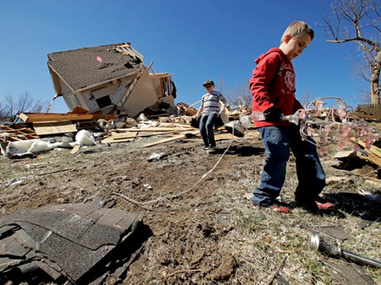 Kadin Lance, right, and his brother Carter Lance pick up debris at a friend's destroyed home Tuesday, March 7, 2017, after a tornado damaged tore through Oak Grove, Mo., Monday night.