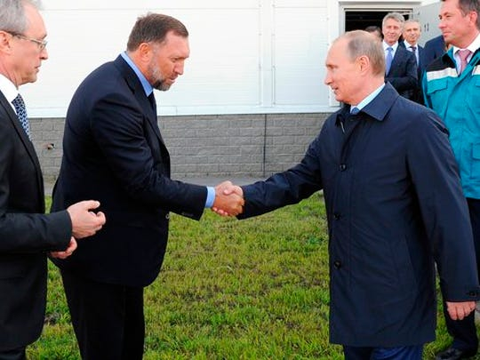 FILE - In this Sept. 19, 2014 file-pool photo, Russian President Vladimir Putin, right, shakes hands with Russian metals magnate Oleg Deripaska while visiting the RusVinyl plant in Kstovo, in Russia's Nizhny Novgorod region. President Donald Trump's former campaign chairman, Paul Manafort, secretly worked for Deripaska, a Russian billionaire, to advance the interests of Putin a decade ago and proposed an ambitious political strategy to undermine anti-Russian opposition across former Soviet republics.