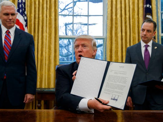 In this Jan. 23, 2017, file photo, Vice President Mike Pence, left, and White House Chief of Staff Reince Priebus, right, watch as President Donald Trump shows off an executive order to withdraw the U.S. from the 12-nation Trans-Pacific Partnership trade pact agreed to under the Obama administration.