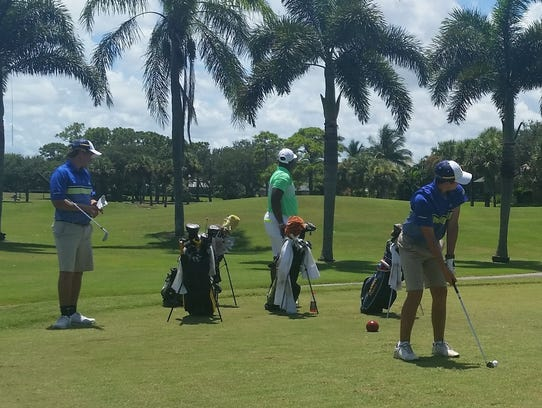 Pine School's Cam Racevicius (right) tees off on the