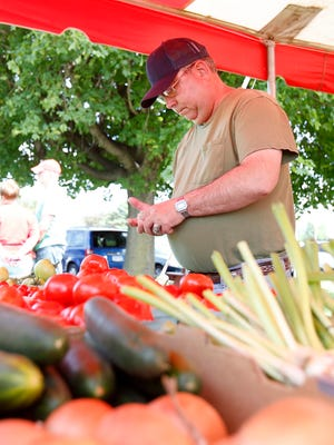 Ken Washburn, of Elmira, purchases a quart of tomatoes Friday at the East Side Farmers Market.