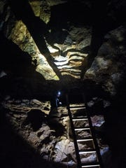 Taylor Woods, a caver from the Northern Rocky Mountain Grotto, waits near the top of a mud-covered ladder leading into the Cathedral Room in Lick Creek Cave on Friday.