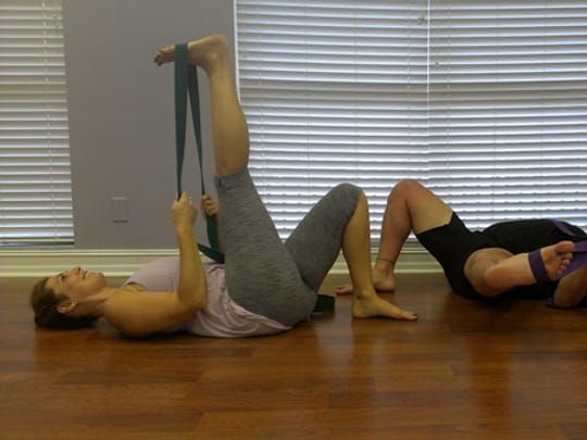 Chiodo and   Simmons demonstrate how to open the hamstrings using a strap.