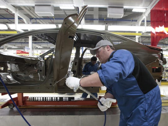 An assembly line worker works on a 2015 Chrysler 200 automobile at the Sterling Heights Assembly Plant in Sterling Heights on Friday, March 14, 2014.
