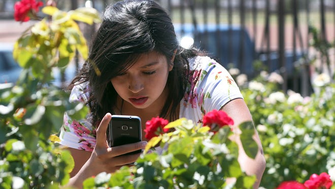 Jacquelin Puebla, 17, of El Paso gets closeup to red roses during a visit to the Municipal Rose Garden at 3418 Aurora at Copia. She was practicing phone camera photography, the 4-acre garden has more than 1,500 rose bushes of more than 400 different types of roses.