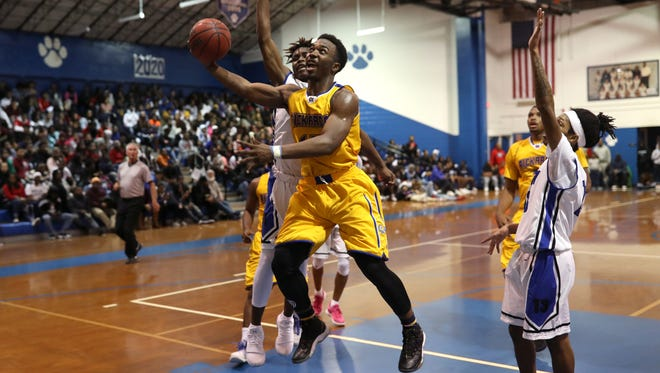 Rickards' Gentry Sparks lays the ball up and in while being fouled by Godby's Taiwan Howard during their game at Godby High School on Friday, Jan. 5, 2018.