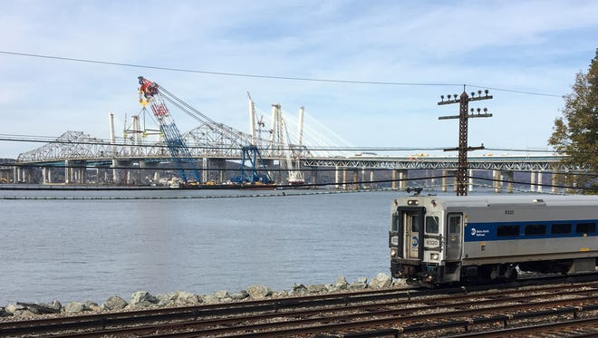 The I Lift NY supercrane is parked near the Westchester shore in front of the new Governor Mario M. Cuomo Bridge and the old Tappan Zee Bridge, as a Metro-North train travels by in Tarrytown, Nov. 4, 2017.