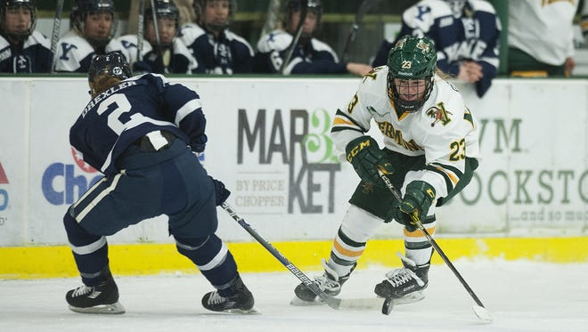 Vermont's Alyssa Gorecki (23) skate past Yale's Kara Crexler (2) with the puck during the women's hockey game between the Yale Bulldogs and the Vermont Catamounts at Gutterson Fieldhouse on Saturday.