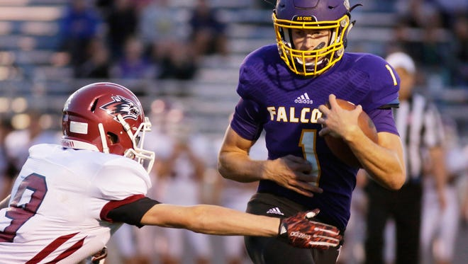 Sheboygan Falls' Jared Petrie (1) carries the ball by New Holstein's Breyden Niec (9) Friday September 1, 2017, in Falls.