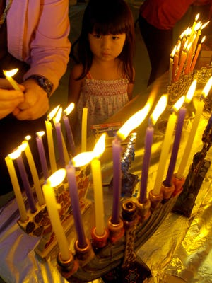 FILE- Kai Griffin, 4, of Melbourne Beach, looks on as her mother, Tracy Griffin, lights the family's menorah