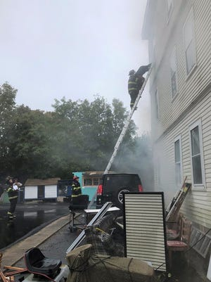 Brockton firefighters responded to a two-alarm blaze at 574 Warren Ave. shortly before 9:30 a.m. on Tuesday, Oct. 13, 2020. Firefighters stretched a line to the basement of the wood-frame triple-decker apartment building, while firefighters rescued four people from the third floor using a ladder.