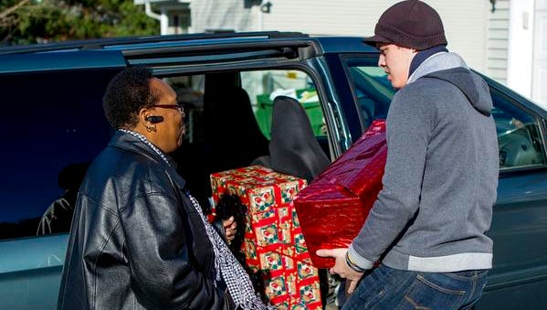 Doreen Bagden, left, a close family friend of the Seidles delivers gifts donated by the Asbury Park Press and NAACP to the Seidle children at their home in Neptune on Dec. 19.