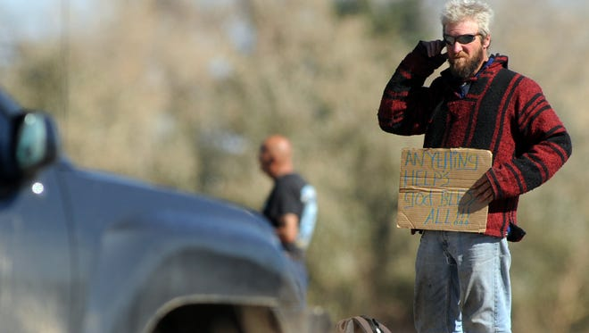 Norman Freel of Fort Collins holds a sign asking for money at the intersection of Mulberry Road and Timberline Road Tuesday Oct. 23, 2012.