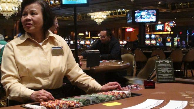 A dealer waits for customers at a card table at the Trump Taj Mahal casino in Atlantic City earlier in May.
