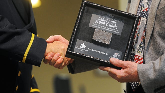 Ed Breen, left, a retired battalion chief with the Fire Department of New York, presents John Pohlmann, manager of Carpet One, with a specially-designed shadowbox containing hallowed 9/11 steel from Ground Zero Monday, Dec. 1, 2015, at Carpet One in Sioux Falls. The Carpet One store in Sioux Falls received the award for their support of the Stephen Siller Tunnel to Towers Foundation's Building for America's Bravest program.