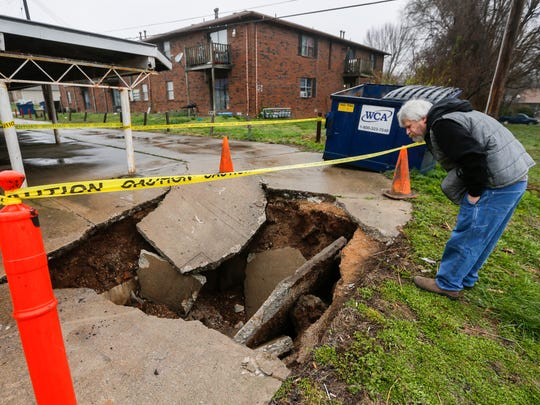 Bryan Posten looks into the hole at his apartment complex where a trash truck fell after the concrete collapsed underneath it near E. University Street on Monday, April, 2, 2018.