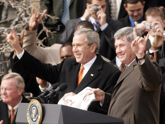 "President Bush, left, displays the ""Hook Em Horns"" signs along with Head Coach Mack Brown, right, on Feb. 14, 2006, during a photo opportunity on the South Lawn of the White House with the 2005 NCAA National Champion football team from the University of Texas at the White House in Washington."
