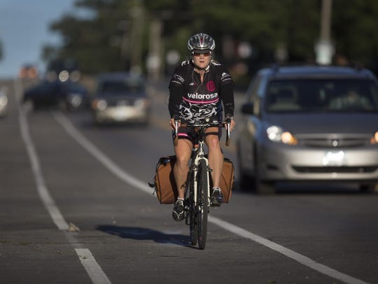 A cyclist navigates the morning commute in the bike lane on Ingersoll Avenue.