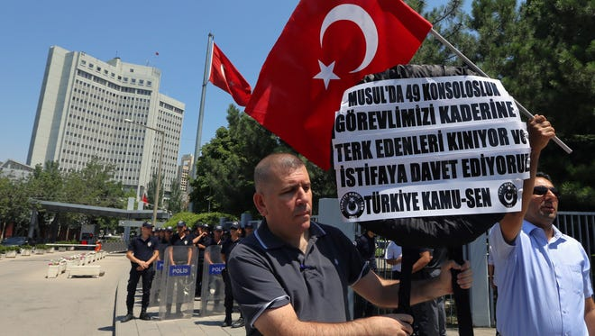 Turkish civil servants stage a protest outside Foreign Ministry, demanding the release of 49 Turkish officials seized in the Turkish consulate in Mosul, northern Iraq in June by Islamic militants, in Ankara, Turkey, Thursday, July 17, 2014.