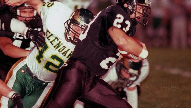 Perry's Eric Heinzer (23) escapes GlenOak's linebacker Steve Nichols during a 2000 football game.