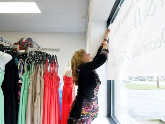 Fashion Cents Consign & Redesign personal assistant Roxanne Taylor hangs up a banner in the Springettsbury Township store's front window on Wednesday. The store recently moved to a new location on East Market Street, and is now accepting furniture and home decor for consignment.