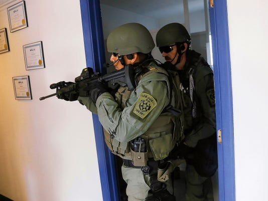 Members of the San Juan County Sheriff's Office SWAT team clear rooms Saturday during a training exercise at Atlantic Avation in Farmington.