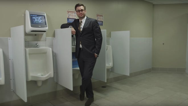 """""""Golden Thrones"""" host Jon DelCollo stands next to urinals equipped with video games at Coca-Cola Park in Allentown, Pa."""