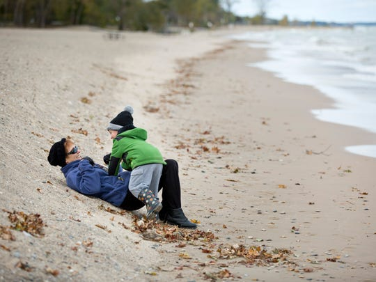 Matthew Kreiner, 3, jumps onto his grandmother Pat Kreiner, of Port Huron Township, as they take a break from walking along the beach Wednesday, October 14, 2015 at Lakeside Park in Port Huron. A new restroom and concessions facility and splash pad will be constructed and open by May of 2016 as part of improvements at the park.