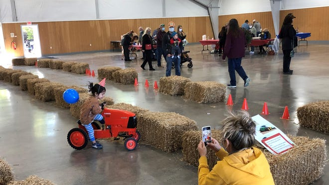 Gia Adams, of Branchville, takes a photo of her daughter Avery, who was celebrating her third birthday, as she rides on a tractor in the Richards Building at the Sussex County Fairgrounds during Rooster's Family Fun Day Saturday.