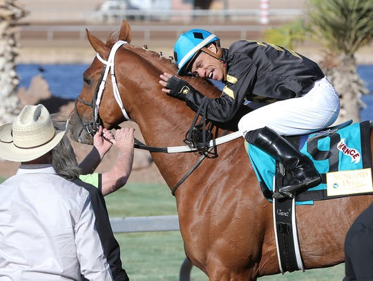Local jockey Alfredo Juarez Jr. hugs Hence after winning
