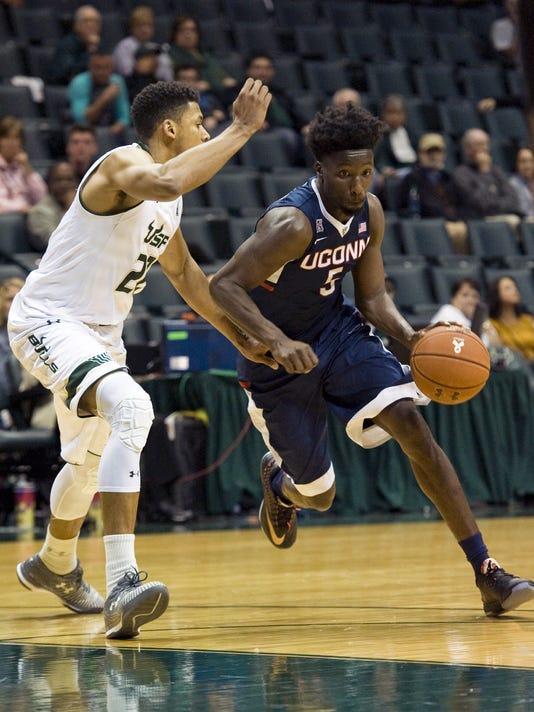 Connecticut's Daniel Hamilton (5) moves the ball under pressure from South Florida's Angel Nunez (22) during the second half of an NCAA college basketball game Thursday, Feb. 25, 2016 in Tampa, Fla. Connecticut defeated South Florida 81-51. (AP Photo/Steve Nesius)