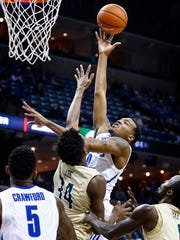University of Memphis forward K.J. Lawson (right) puts up a shot over UAB defender William Lee (left) during second half action at the FedExForum.