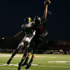 Damien Sharpe, left, and Rhett Layton, right, fight for the ball during the opening football game at Williams Field High School in Gilbert on Aug. 22, 2014.