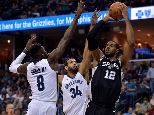 San Antonio Spurs forward LaMarcus Aldridge (12) shoots against Memphis Grizzlies forwards Brandan Wright (34) and James Ennis III (8) during the first half of an NBA basketball game Friday, Dec. 1, 2017, in Memphis, Tenn. (AP Photo/Brandon Dill)